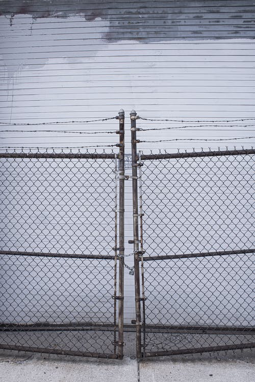 Gray Metal Fence Under White Sky