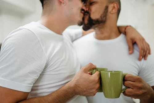 Two Men Holding Cups and Kissing