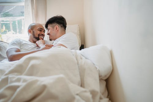 Two Men Smiling in Bed Together