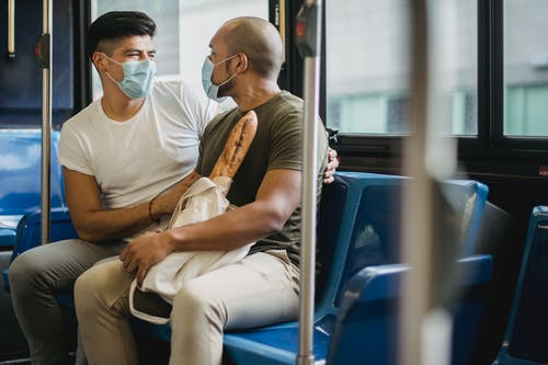 Two Men Wearing Face Masks Sitting in Public Transportation