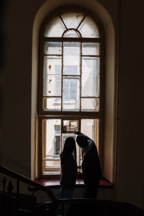 Man in Black Jacket Standing Beside Window
