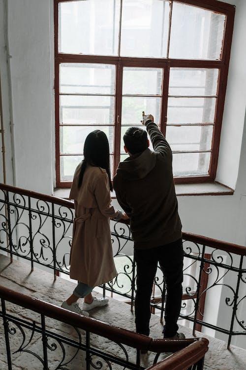 Woman in Brown Coat Standing Near Window
