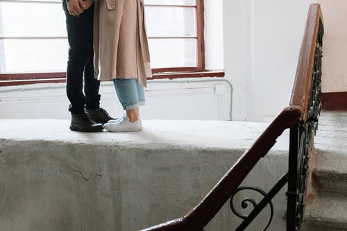 Woman in Brown Coat and Blue Denim Jeans Standing on Gray Concrete Staircase