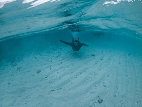 Faceless person diving in blue seawater