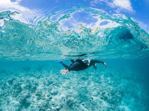 Anonymous snorkeler swimming in azure seawater