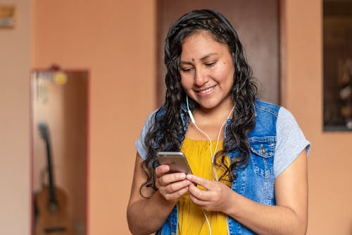 Woman in Blue Denim Vest Holding Gold Iphone 6