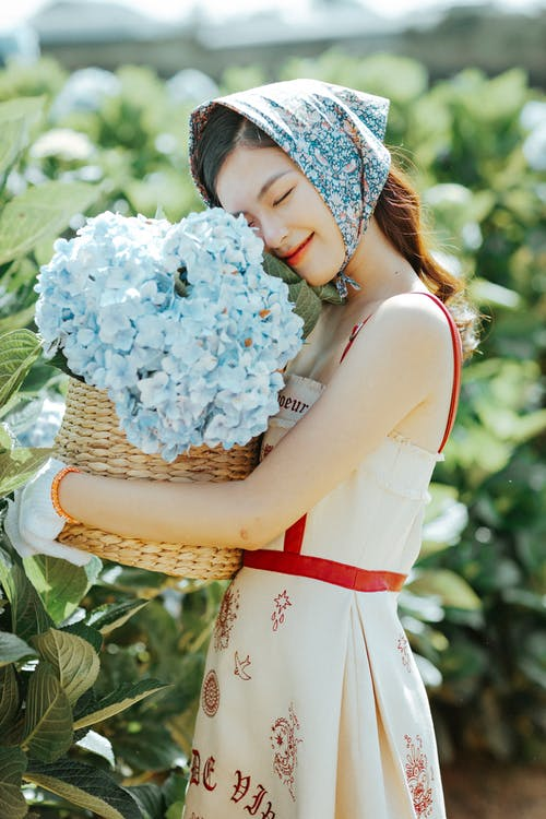 Cheerful Asian woman smelling flowers