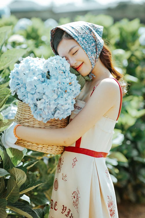 Side view of pleased Asian female gardener in headscarf standing with eyes closed near green bushes with flowers in wicker bucket in hands