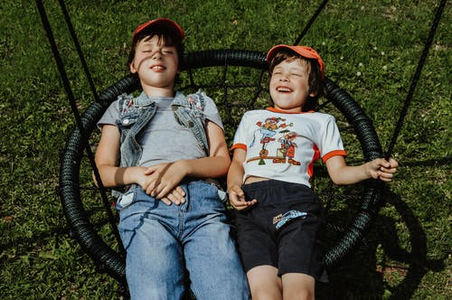 From above of happy boys with closed eyes wearing caps lying on round swing on grassy lawn while having fun in yard