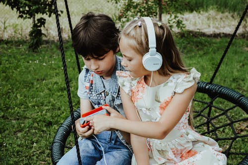 Attentive girl with headphones and serious boy with retro cassette player listening to songs while sitting on swing in grassy park