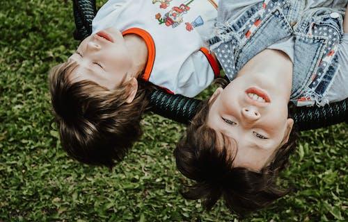 Content boys lying on swings