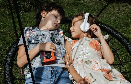 From above of cheerful girl with headphones looking at boy with vintage cassette player while lying on swing together and listening to songs
