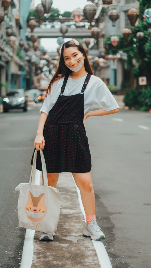 Full body young Asian female in casual wear and protective respirator standing with hand on waist on busy city street and looking at camera