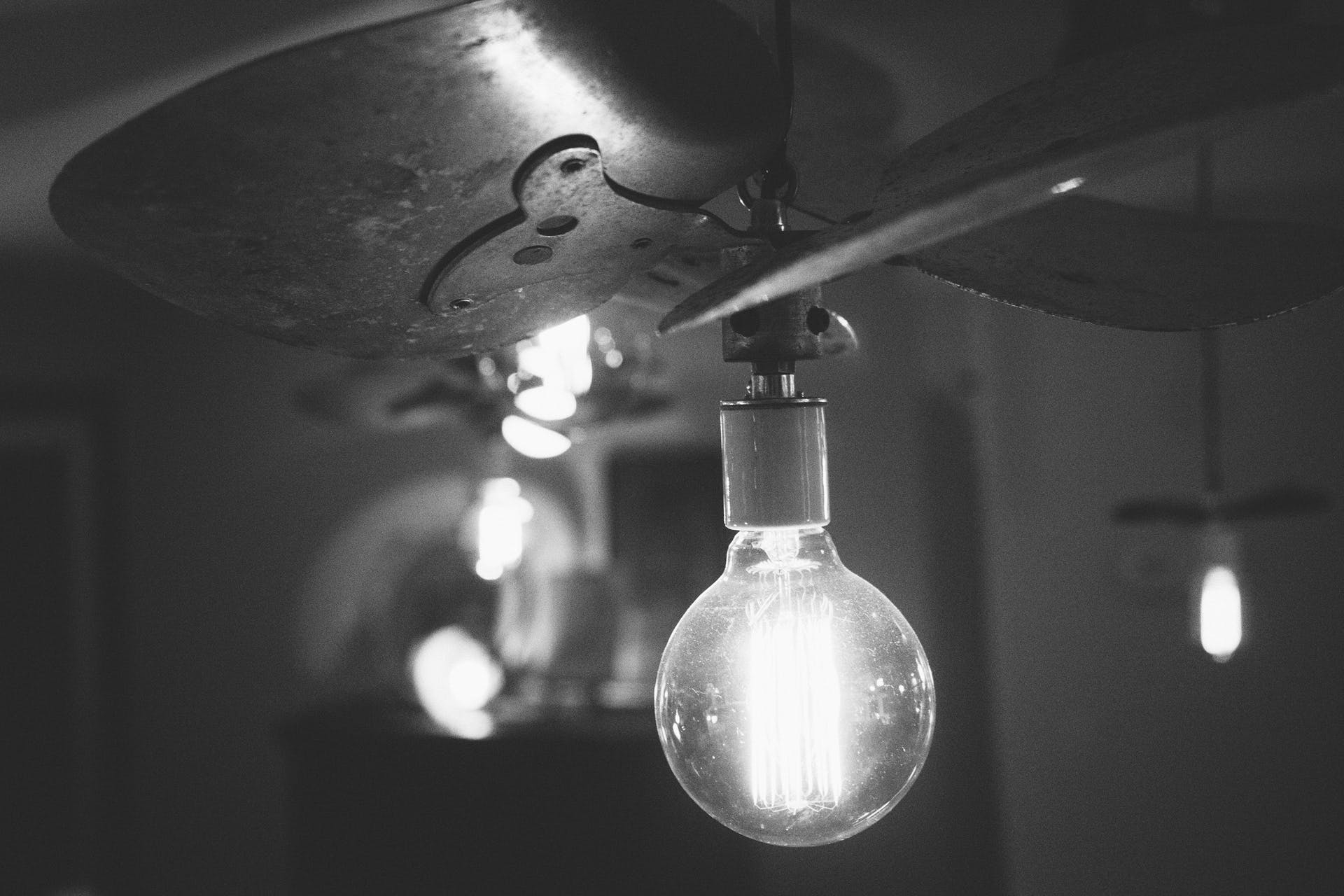 Grayscale Photography of Turned on Light With Ceiling Fan