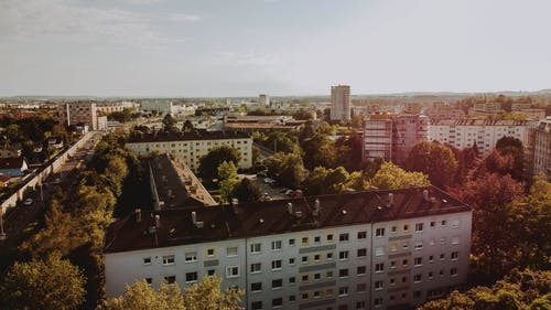Drone view of town with typical architecture surrounded with greenery and growing plants