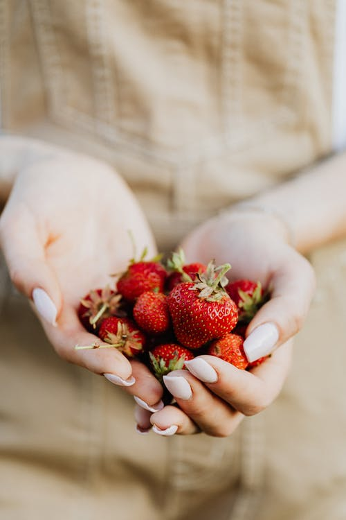 Woman Holding Red Strawberries in Close Up Photography
