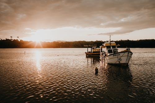 Scenery view of fishing boats on rippled river under cloudy sky with shiny sun in twilight
