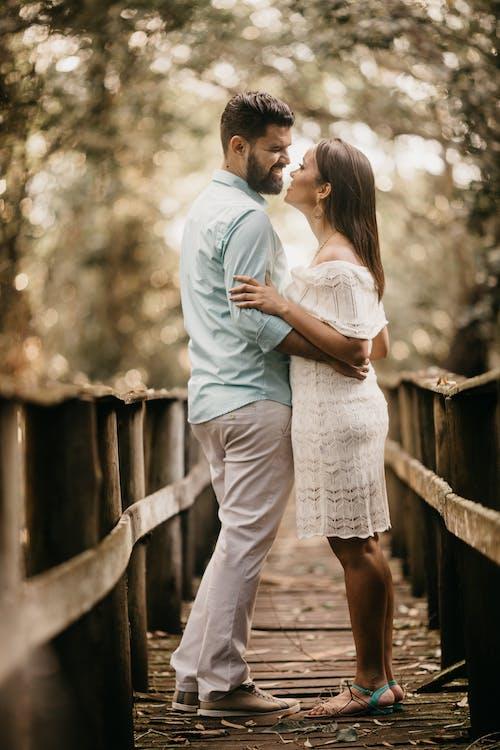 Stylish smiling couple embracing on narrow walkway