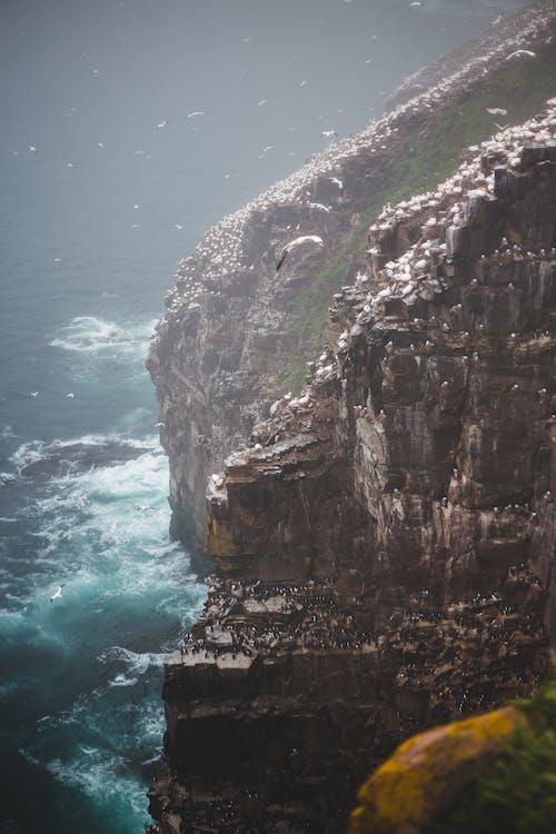 Rough rock near foamy ocean in stormy weather