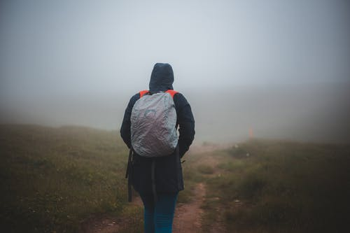 Unrecognizable tourist with rucksack walking on shabby path in fog
