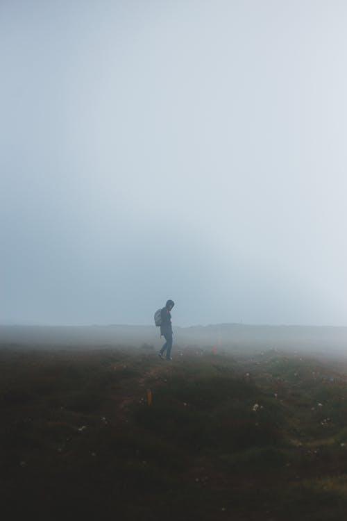 Lonely person walking in foggy field