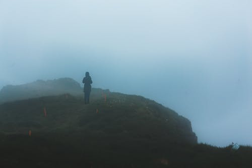 Unrecognizable traveler on hill in fog