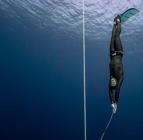 Man diving in deep blue sea water