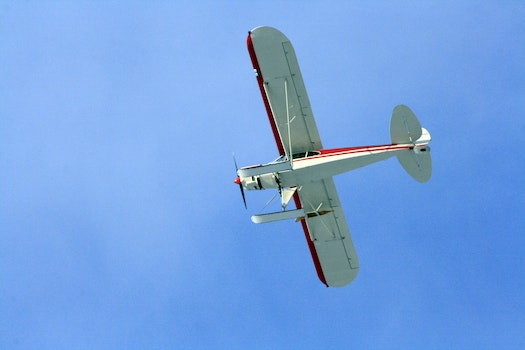 White and Red Airplane Under Blue Sky during Daytime