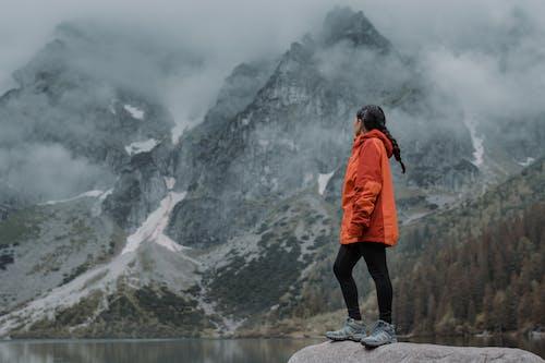 Person in Orange Jacket Standing on Rock