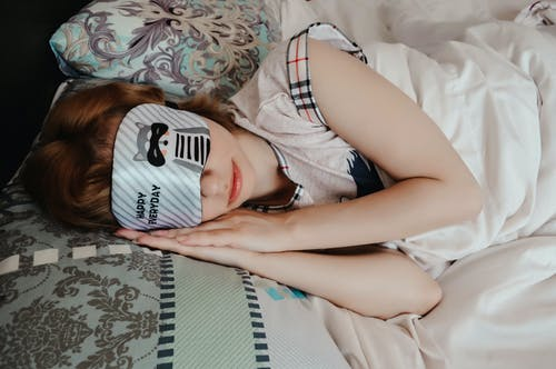Anonymous female covering eyes with sleep mask taking nap while lying on bed under blanket in cozy bedroom at home