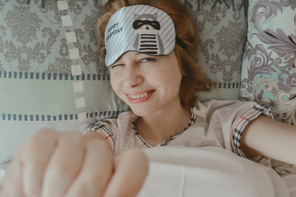 Top view of joyful female reaching out hands to camera and blinking while lying on bed under blanket and looking at camera