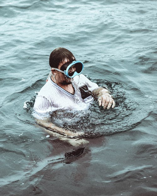 Man in mask swimming in water