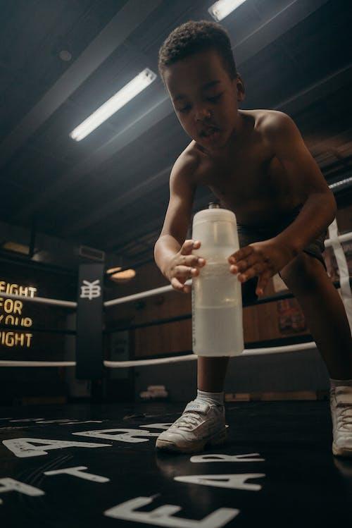 Topless Man Holding White Plastic Bottle