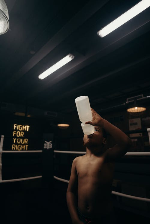 Topless Man Holding White Plastic Cup