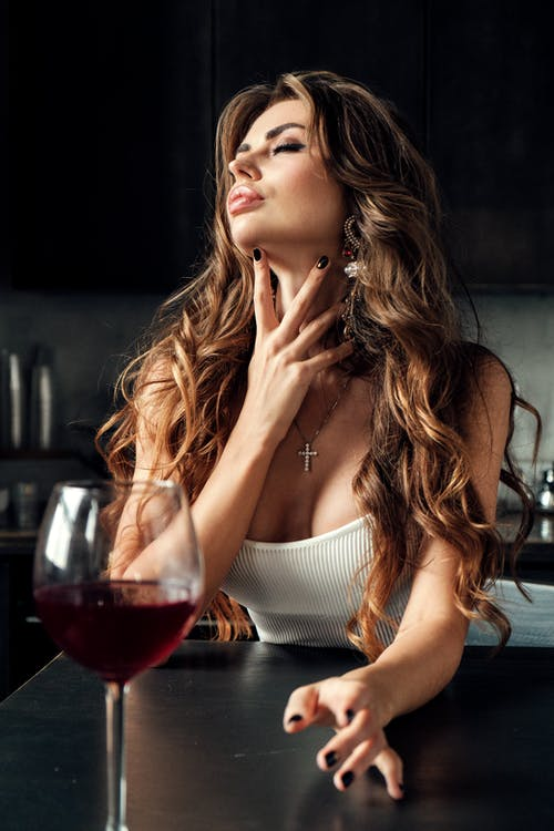 Alluring young lady relaxing in kitchen with wine glass
