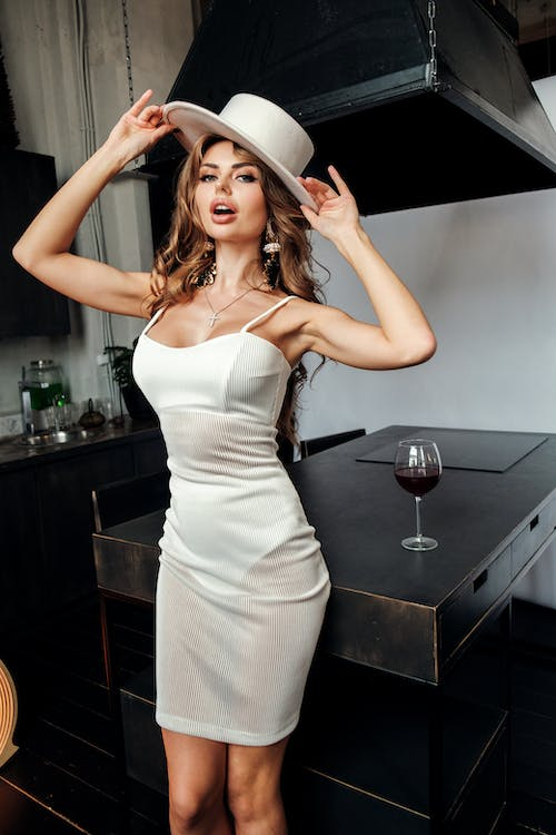 Sensual young woman adjusting hat while resting in kitchen near table with wineglass