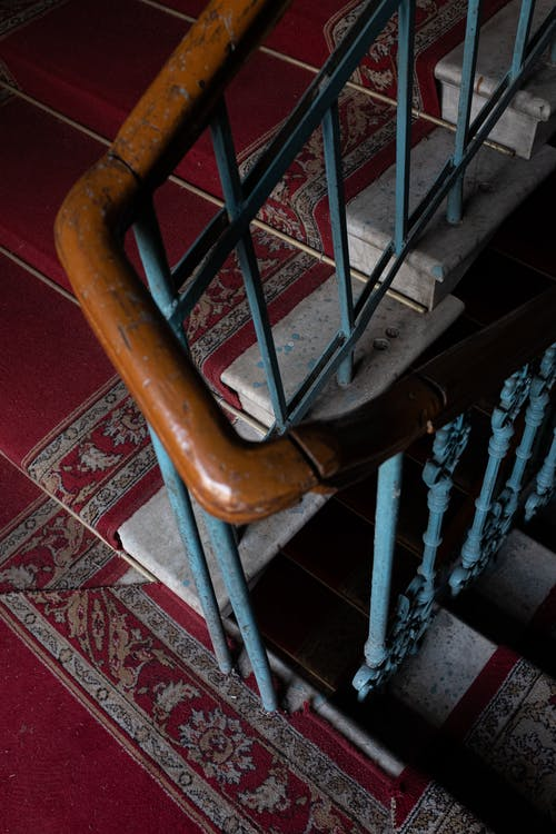 Brown Wooden Staircase on Red and White Floral Area Rug