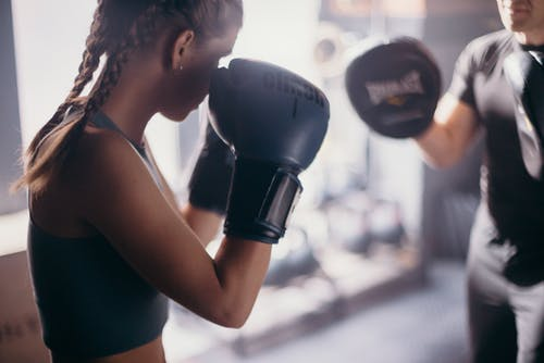 Woman in Black Tank Top Wearing Black Boxing Gloves
