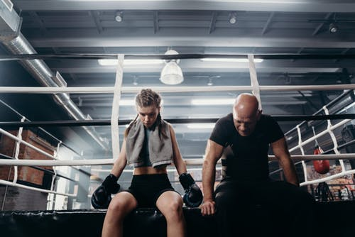 Man in Black T-shirt and Black Shorts Sitting on Black Exercise Equipment