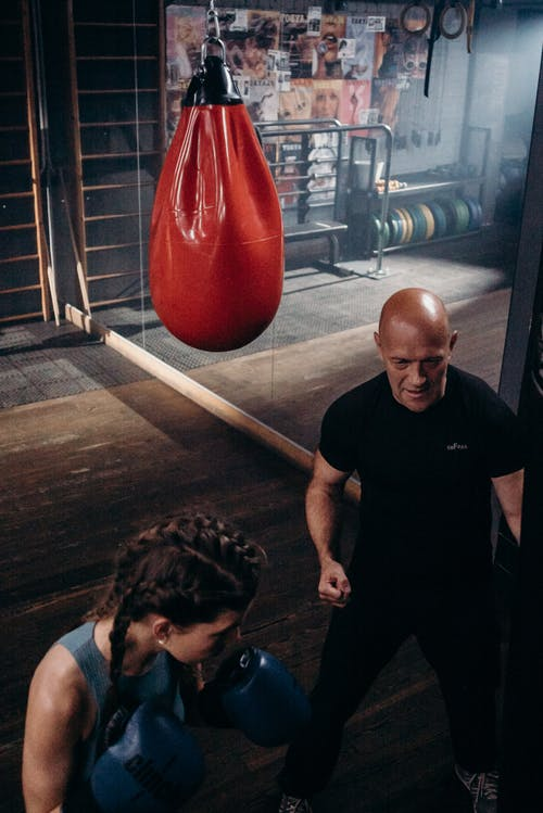 Man in Black Crew Neck T-shirt and Black Shorts Holding Red Boxing Gloves