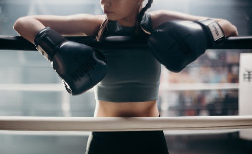 Woman in Black Sports Bra and Black Shorts Holding Black and White Boxing Gloves