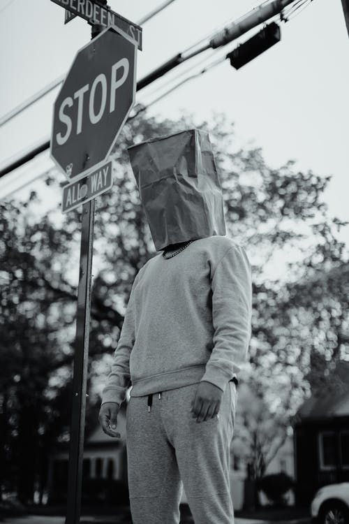 Grayscale Photo of Man in Jacket Standing on Stop Sign