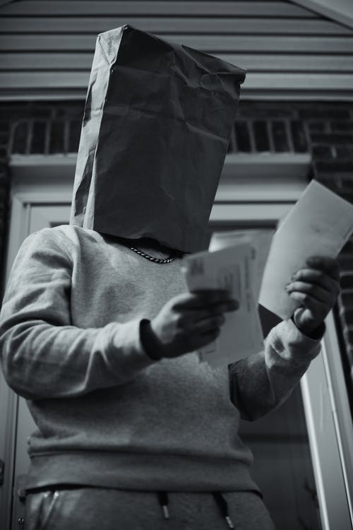 Grayscale Photo of Man Holding Paper