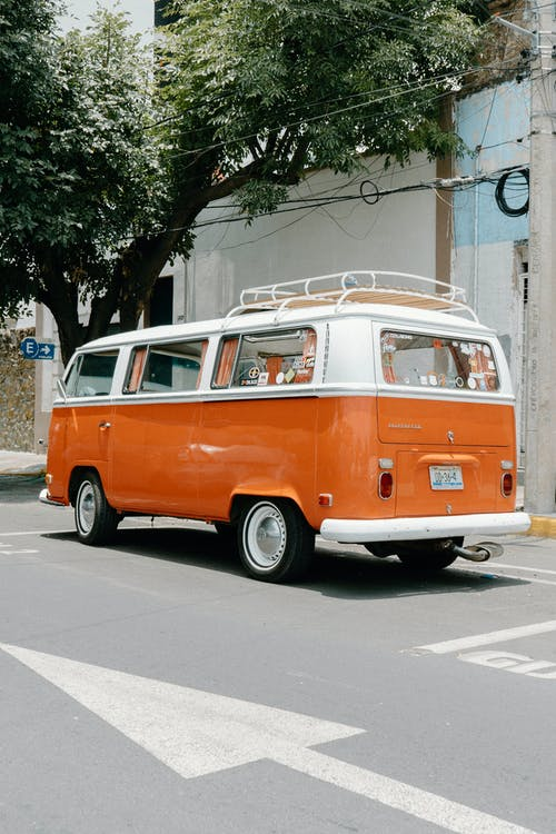 Orange and White Volkswagen T-2 Parked on Sidewalk