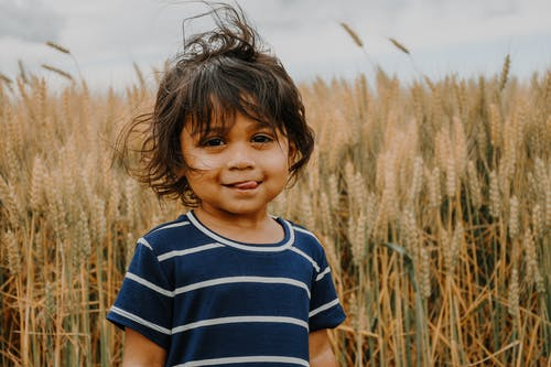 Boy in Blue and White Striped Crew Neck T-shirt Standing on Brown Wheat Field during