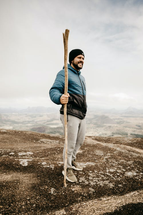 Full body of happy bearded male in outerwear with stick in hand standing on rough terrain under cloudy sky in gloomy weather