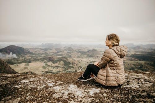 Woman enjoying view of mountainous terrain