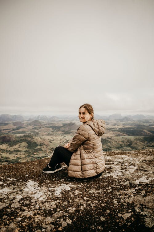 Joyful female tourist in warm outfit sitting on rocky ground above mountainous terrain under gray sky and looking away
