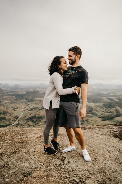 Full length delighted young couple in casual wear embracing and laughing while standing on tall hilltop against scenic green hilly valley