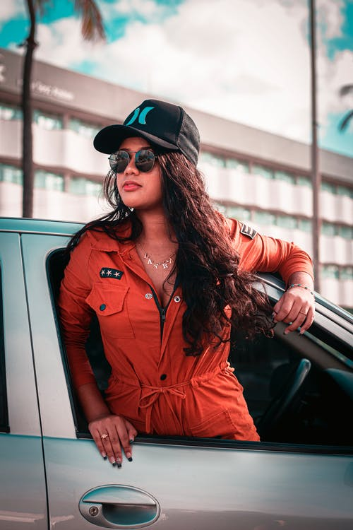 Young stylish ethnic female with long hair in sunglasses and fashionable outfit looking away in window of automobile on street